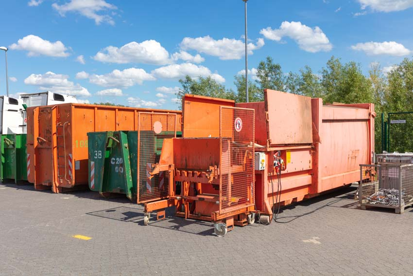 orange waste compactors are standing on a factory site with other waste containers next to them